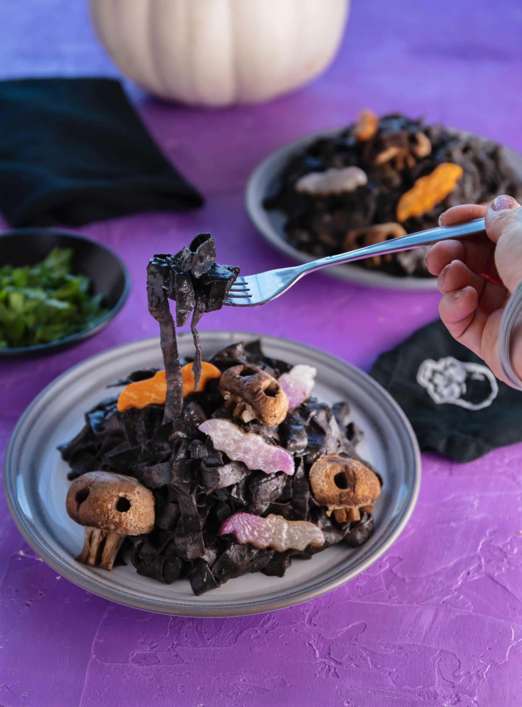 taking a bite of black halloween pasta with veggie bats and skull mushrooms