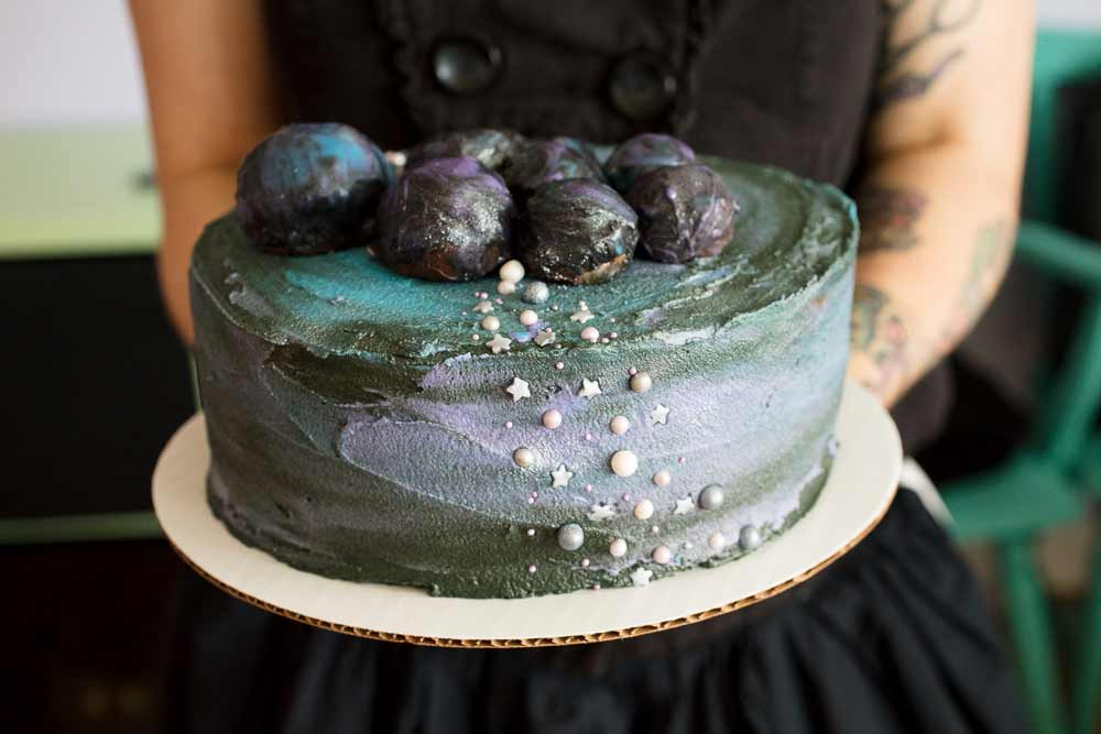 vegan chocolate cake with galaxy buttercream frosting and cookie dough asteroids on top