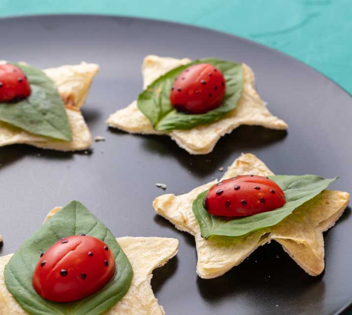 grape tomatoes decorated like ladybugs witting on basil leaves on top of a star-shaped tortilla chip