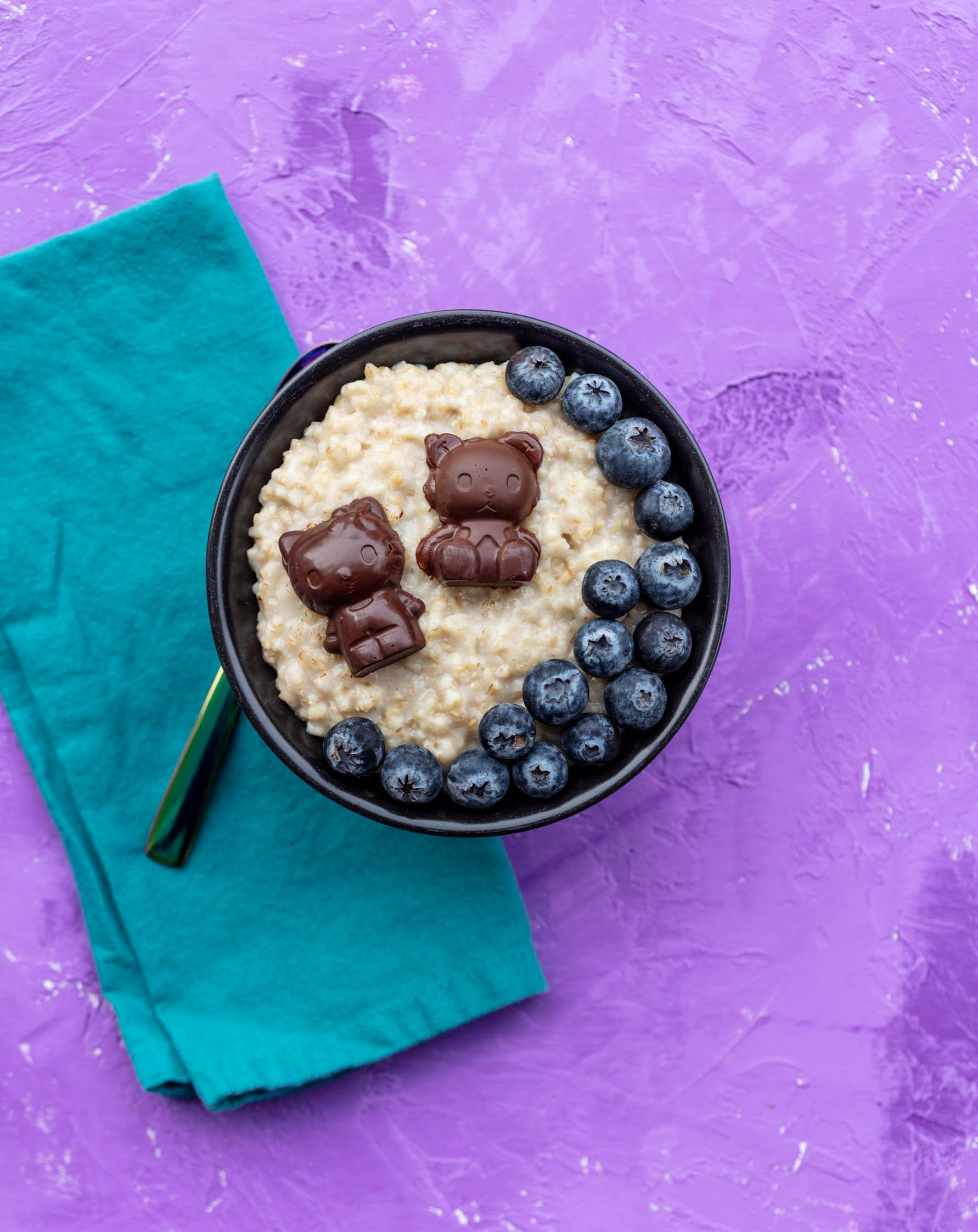 bowl of steel cut oatmeal with hello kitty chocolates and blueberries