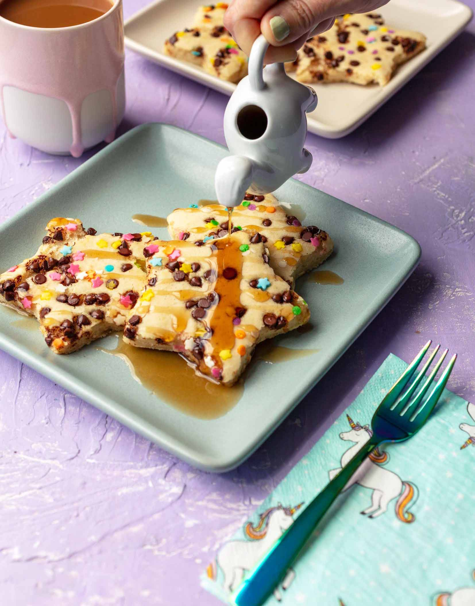 star shaped funfetti chocolate chip pancakes with maple syrup being poured on them