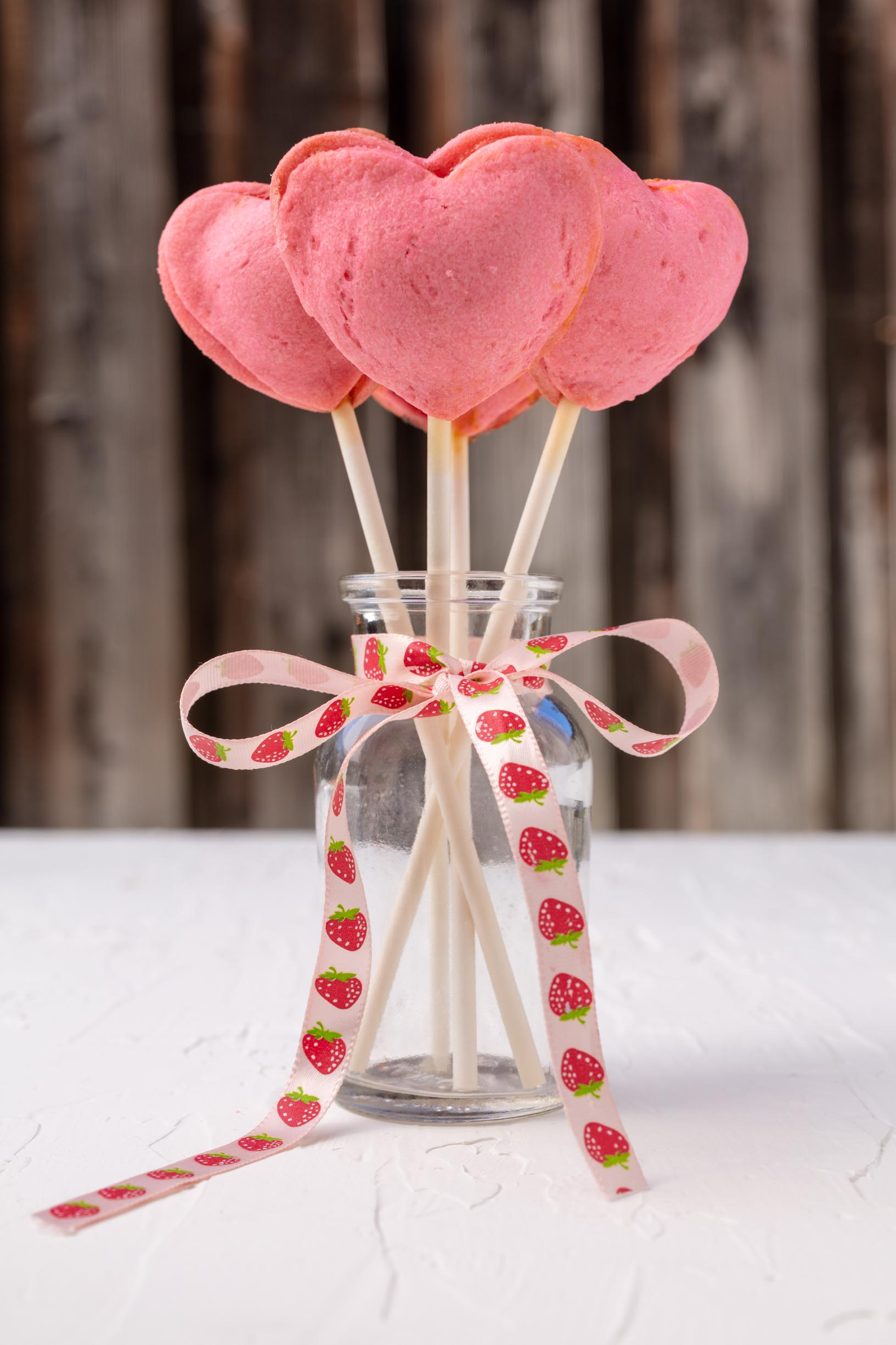 pink heart shaped pie pops sticking out of a jar tied with a bow