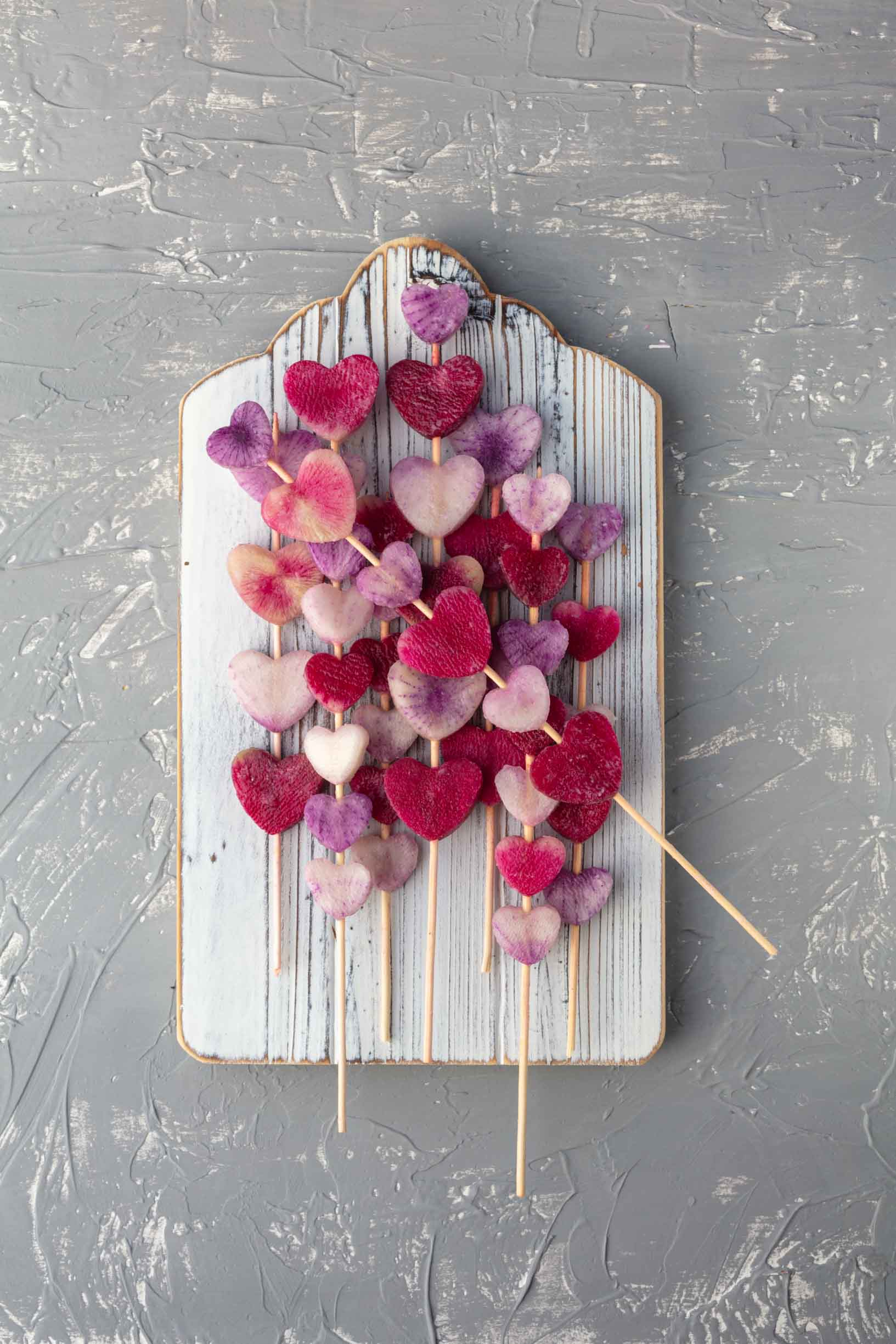 threading the radish hearts onto skewers