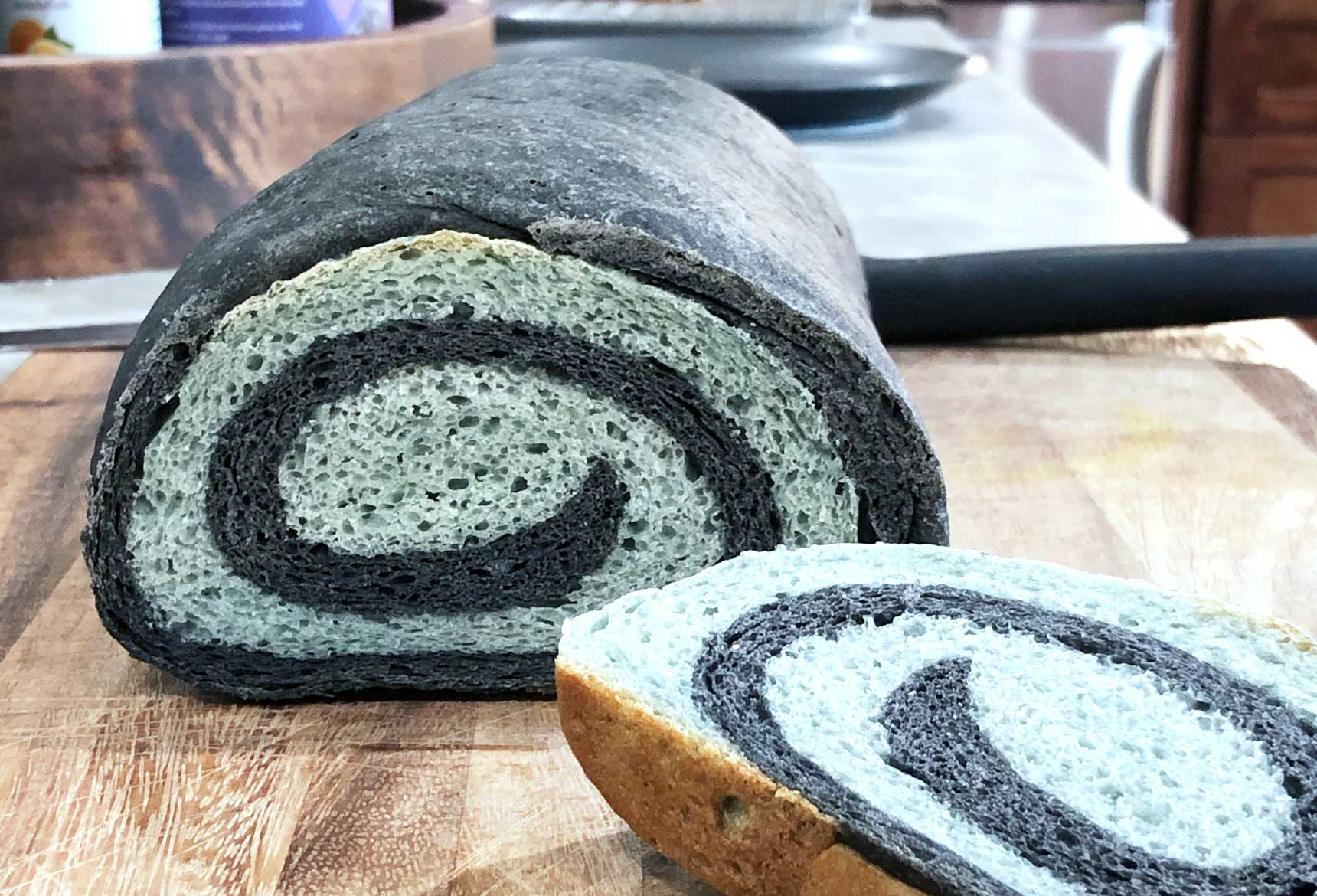 loaf of black and blue swirl bread with one piece sliced showing the spiral